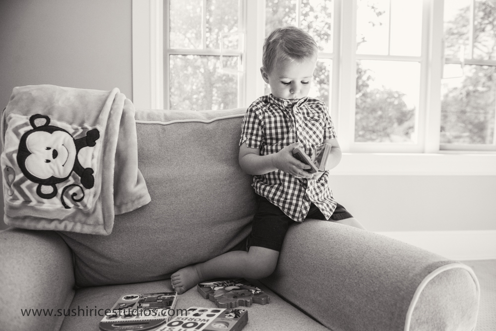 Toddler looking at a book on the couch