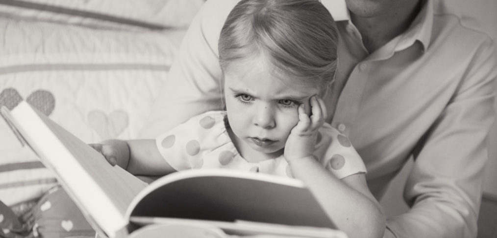 Little girl concentrating on her book