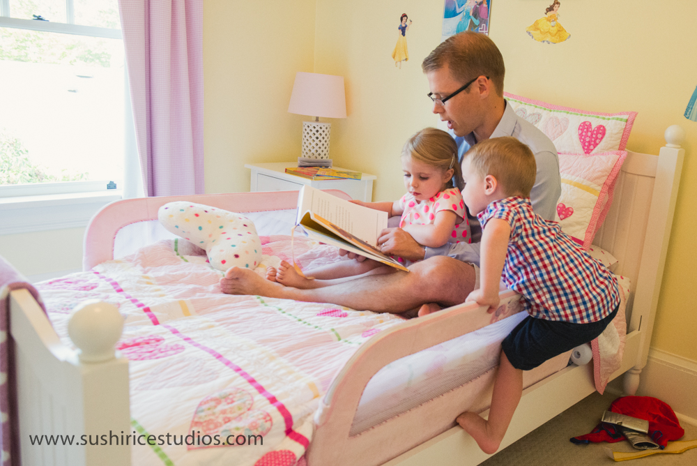 Story time on girls bed while younger brother climbs