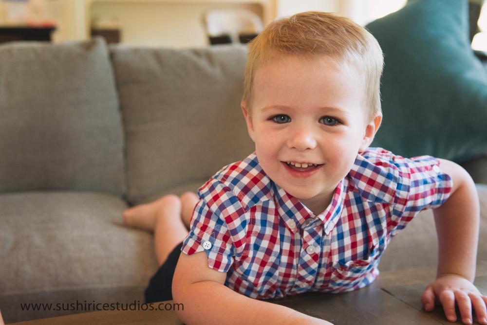 Boy climbing on furniture smiling at camera