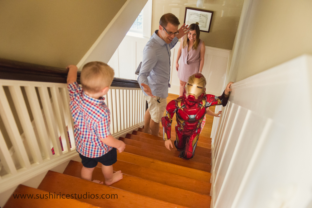 Family watches as a mini iron man climbs stairs