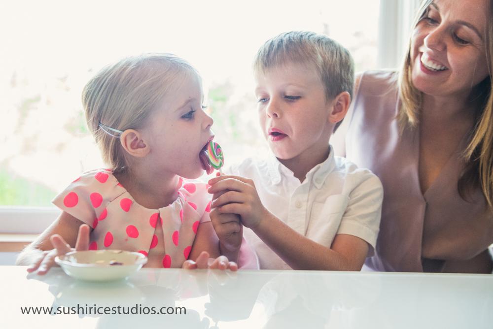 Boy holds lollipop while sister licks