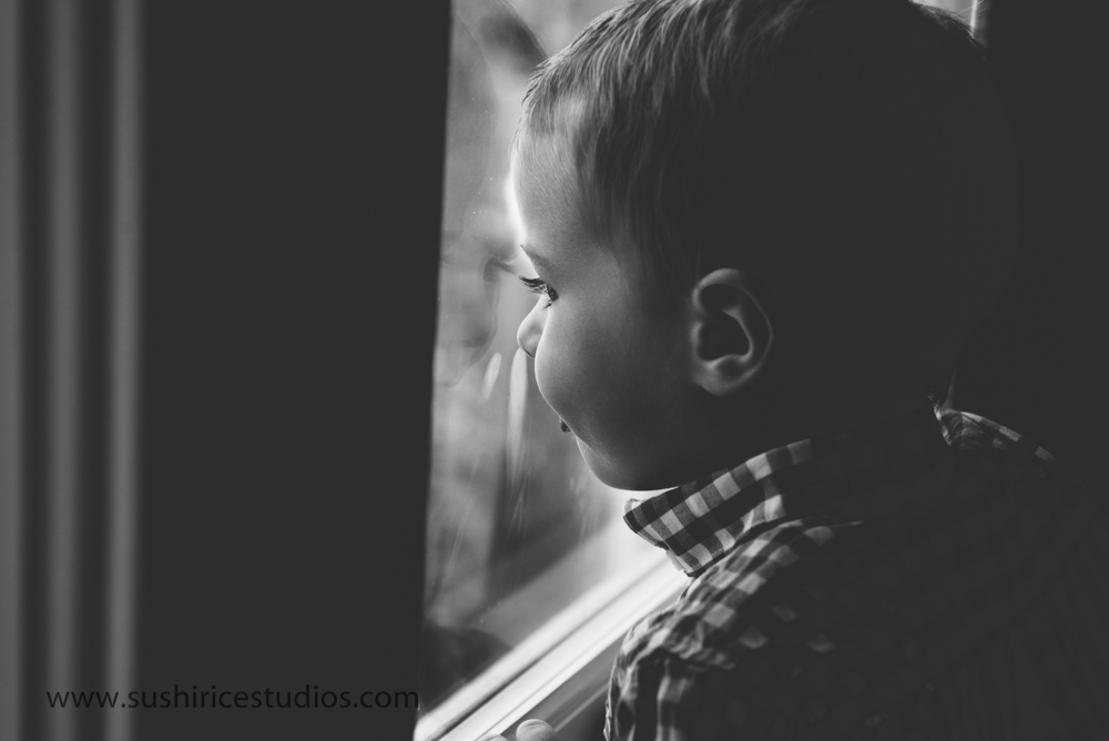 Boy looking out the window with tongue out