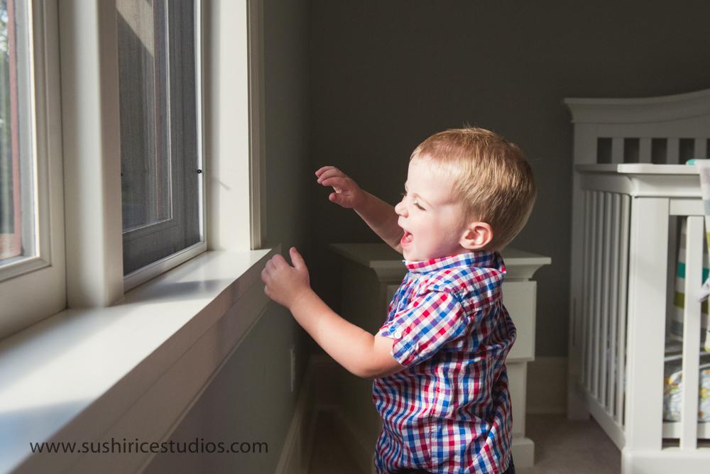 Toddler laughing near window