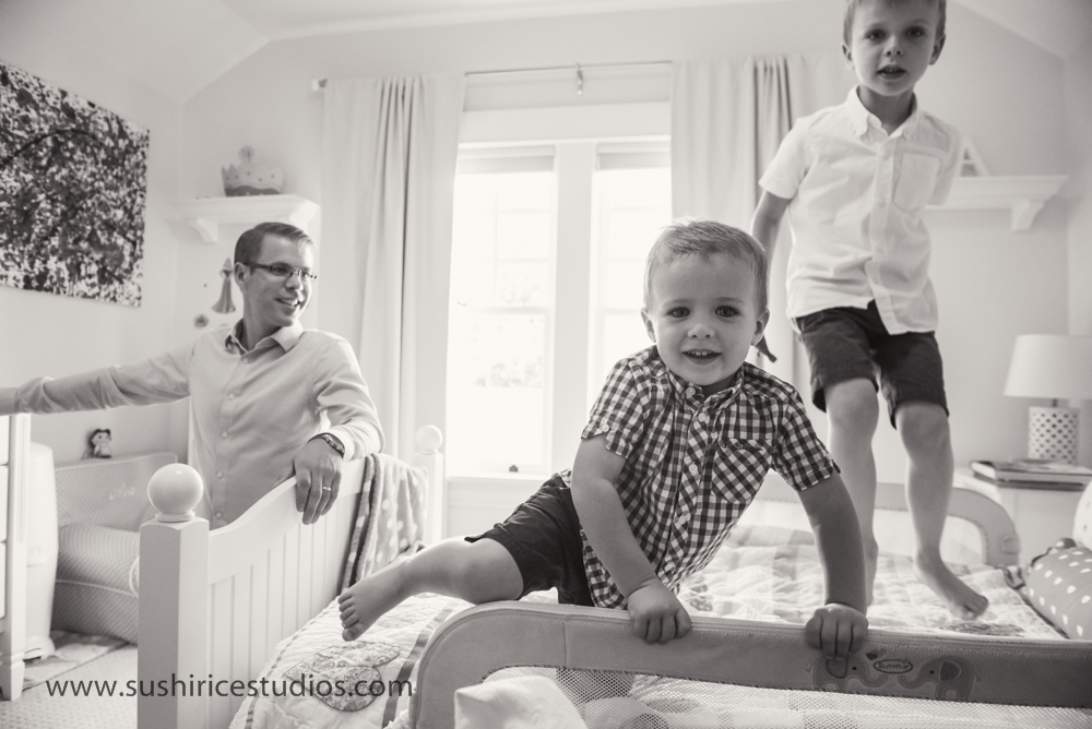 Brothers climbing on sister's bed while dad looks on