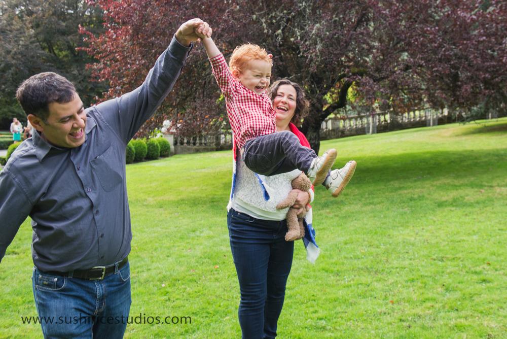 Toddler swinging between parents