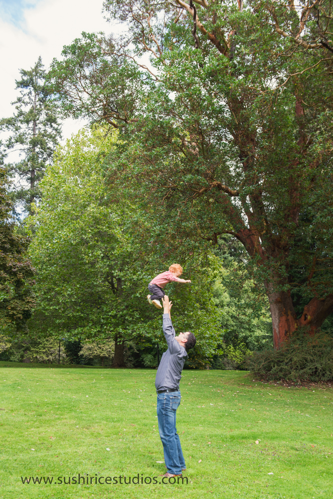 Dad throwing toddler in the air.