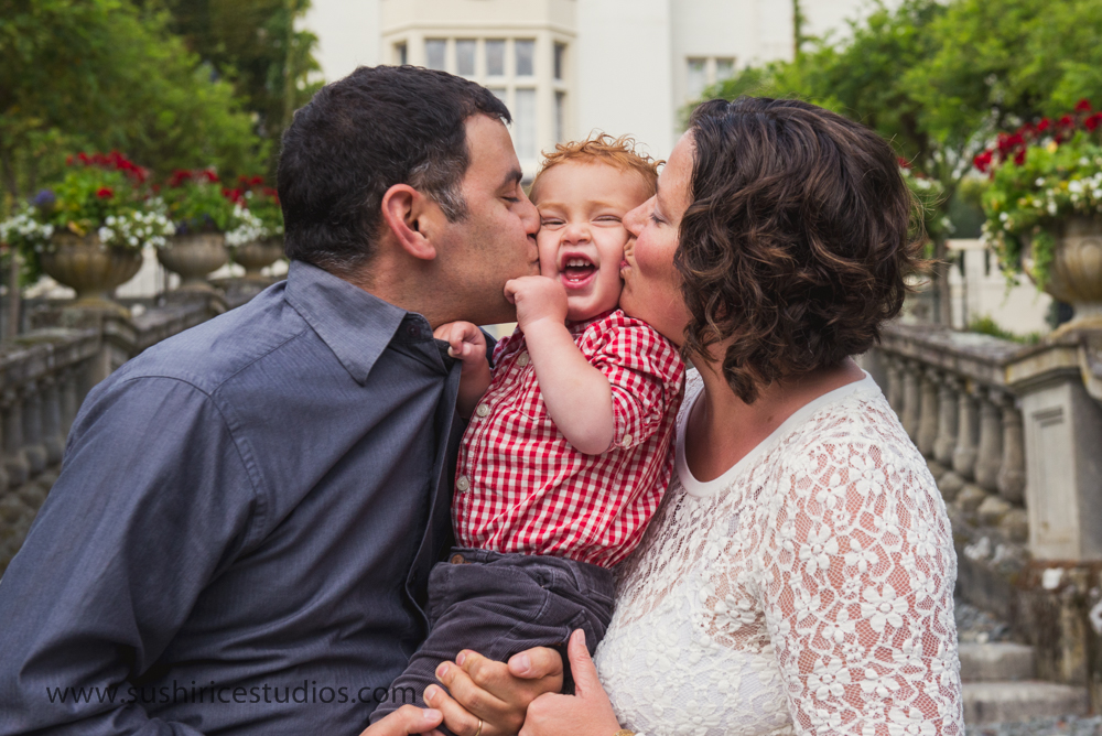 Mom and dad smooshing and kissing toddler