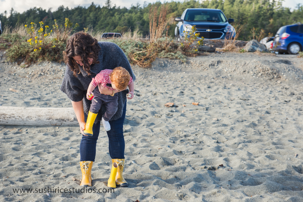 Mom taking off boy's yellow rubber boots