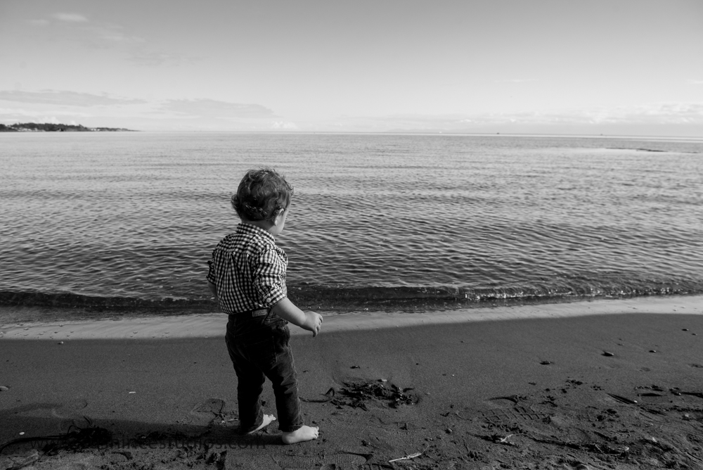 Toddler looking at ocean in black and white