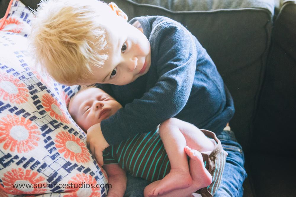 Big brother hugging newborn
